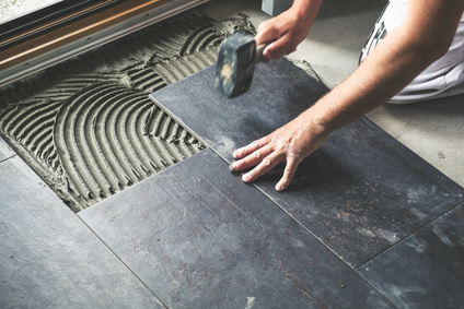 Worker placing ceramic floor tiles on adhesive surface